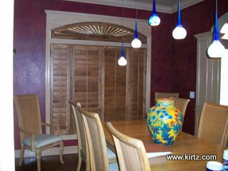 plantation shutters and eyebrow arch were stained to match wood flooring and other accent pieces in the home
